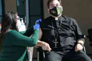 Masked bishop getting vaccinated